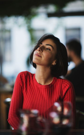 Young woman looking away while sitting indoors