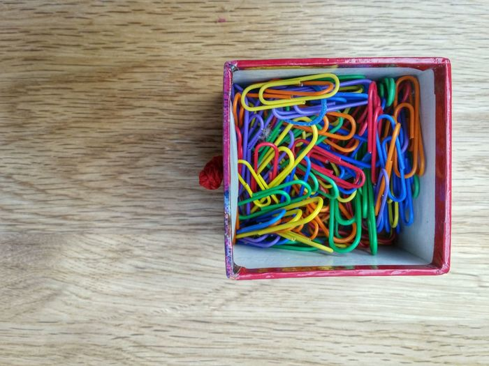 Directly above shot of paper clips in box on table