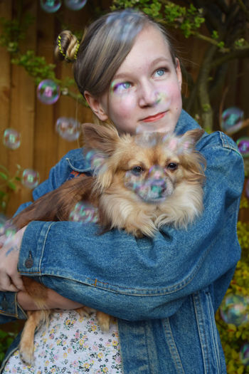 Bubbles Flying Over Thoughtful Girl Holding Dog At Yard