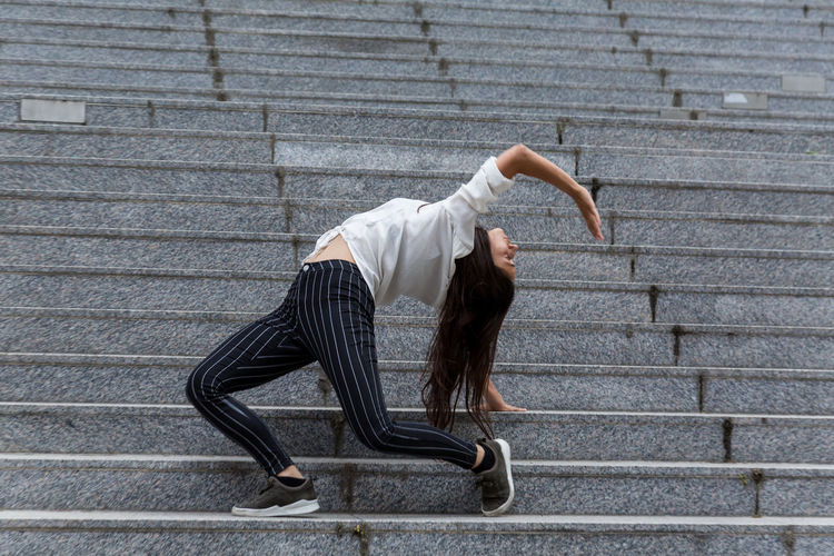 Young woman in dance pose on staircase One Person Staircase Young Adult Long Hair Steps And Staircases Dancing Side View Full Length Day Natural Lighting Profile View Dance Pose Real People Young Woman Indian Ethnicity Outdoors Daylight Flexibility Youth Culture