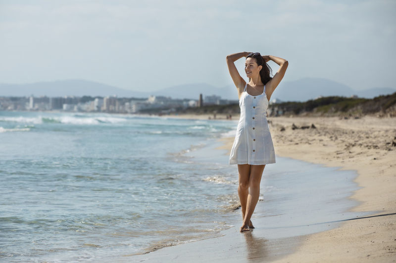 Full length of woman standing at beach against sky