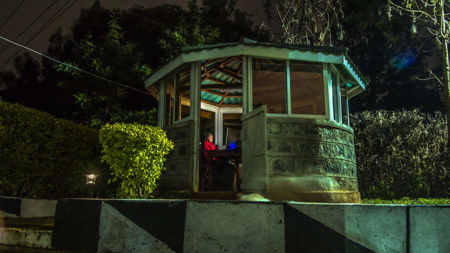Woman Using Computer While Sitting In Gazebo At Night