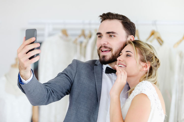 Smiling young couple taking selfie while standing at boutique