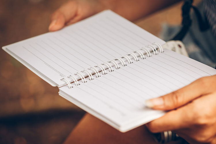 Cropped image of woman holding spiral notebook