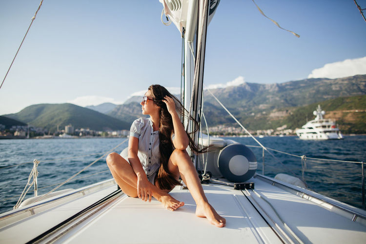 Young Woman Sitting On Boat Sailing In Sea