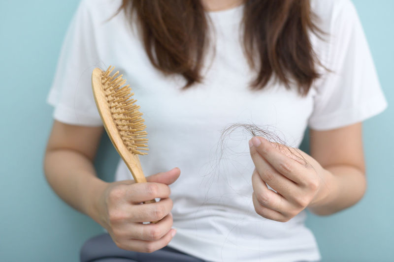 Midsection of woman holding brush with hair against blue background
