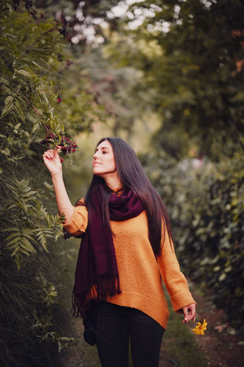Young woman holding flower standing in forest