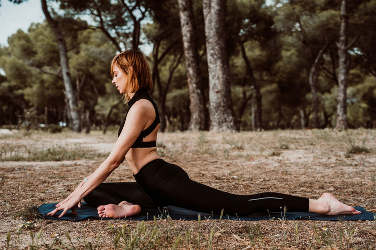 Young and pretty woman doing yoga outdoors in the middle of nature a nice spring afternoon. Relaxation, deep breathing and calm. Lifestyle. Selective focus. Afternoon Blond Yoga Healthy Relaxation Summer Nature Beautiful Female Young Girl Body Exercise Park Pose Grass Sport Beauty Outdoors Meditation Lifestyle Health Green Fitness Morning Lotus Vitality Outdoor Balance Meditating Sunlight Sunset Concentration Slim Relax Wellness Caucasian Active Calm Peaceful Sun Natural Life Training Happiness Recreation  Spring Energy Zen Resting