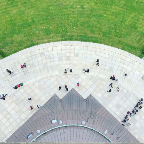 High Angle View Of People Walking On Pathway By Lawn