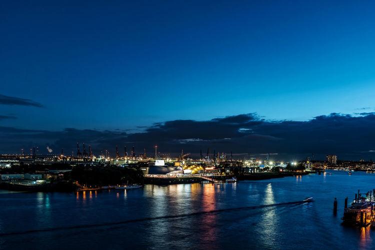 Illuminated City By Sea Against Blue Sky At Dusk