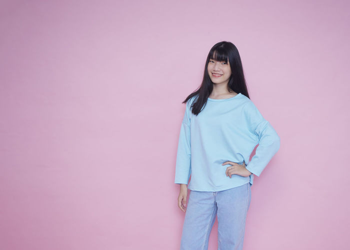 Portrait of woman standing against pink background