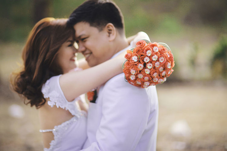 Side View Of Bride Holding Bouquet Embracing Groom On Field