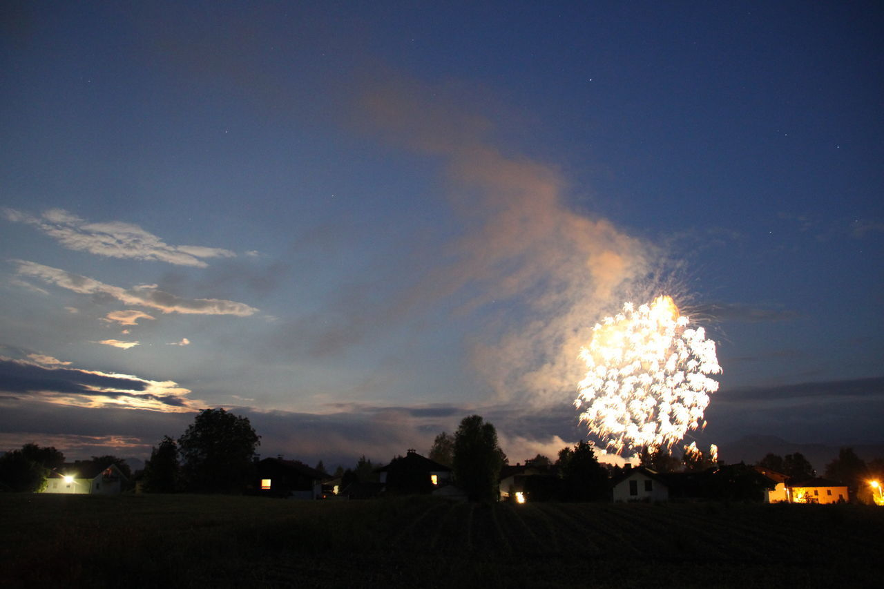 sky, night, illuminated, cloud - sky, nature, no people, silhouette, scenics - nature, outdoors, beauty in nature, environment, field, glowing, tree, landscape, celebration, land, dusk, sunset, building exterior, firework, firework display