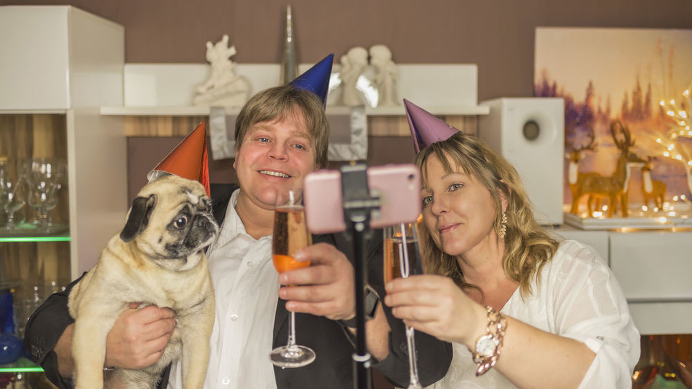 Middle aged couple makes with their pug a selfie during a New Year's Eve party at home At Home Couple Glasses Mobile Phone New Year's Eve Pug Celebration Cell Phone  Champagne Cheers Christmas Decoration Dog Flat Greetings Happy New Year Living Room Middle Aged Party Photography Real People Round Shape Selfie Selfie Stick Smiling Social Media