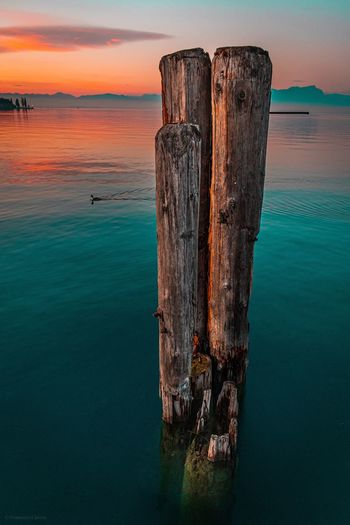 Wooden post in sea against sky during sunset