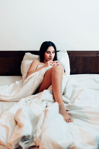 Female person with cup in bed. young woman holding mug of drink and relaxing on bed in duvet at home