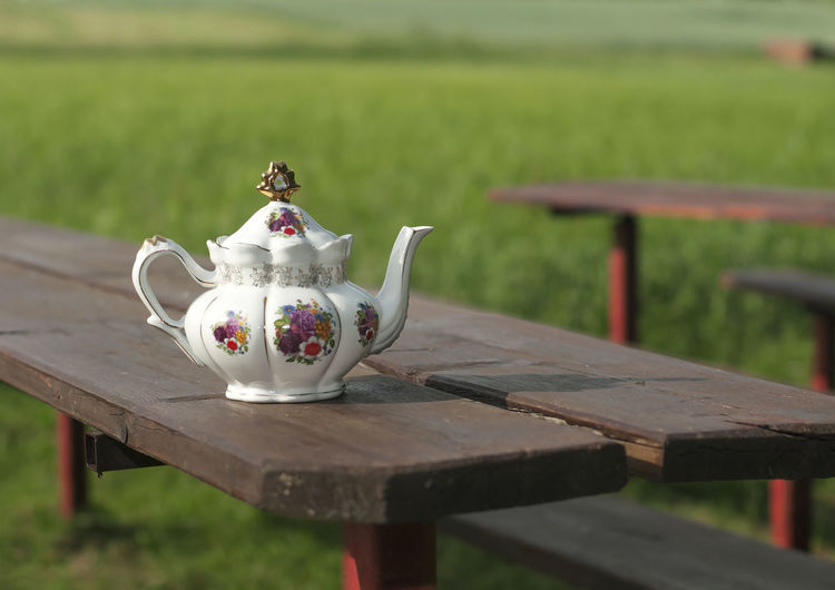 Close-up of teapot on picnic table at park
