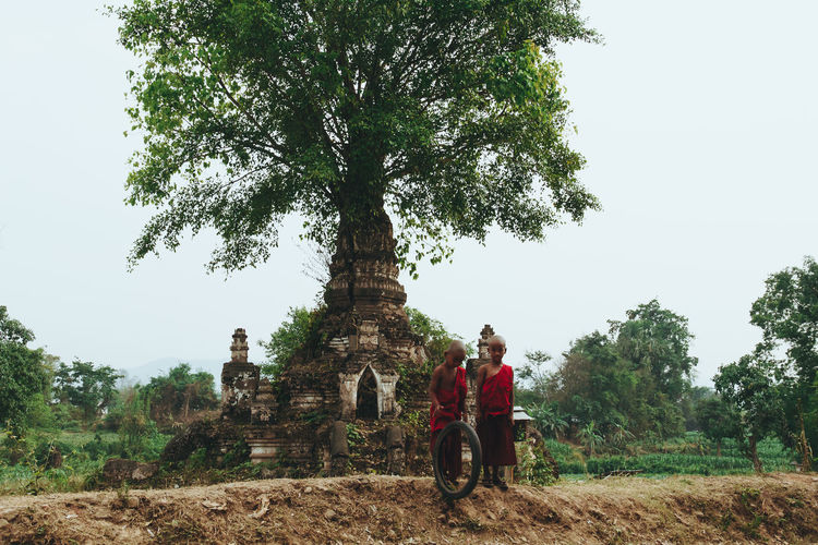 Two child monks play near a temple with a tree growing out of it. - IG @LostBoyMemoirs (Photos taken on Canon 650D Rebel T4i, edited in Lightroom.) People People Watching People Photography Streetwise Photography Street Photography ASIA Myanmar Burma Myanmar Culture Myanmarphotos Adventure Backpacking Culture And Tradition Cultures Exploration Travel Destinations Buddhism Buddhist Monk  Tree Plant Real People Nature Sky Clear Sky Lifestyles Day Growth Two People Land Field Outdoors Leisure Activity Men Adult Travel Rear View Women The Art Of Street Photography