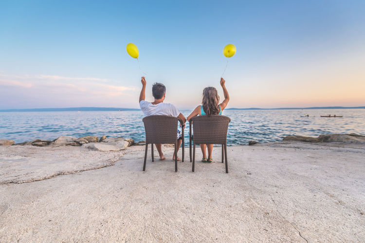 Rear View Of Man And Woman Holding Balloons While Sitting On Chairs At Beach