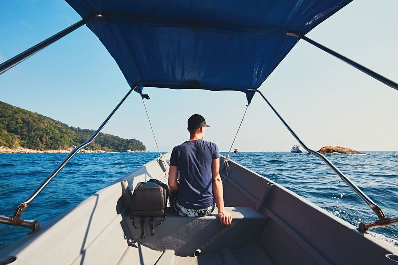 Adventure on the sea. Young man traveling by motorboat. Adventure Backpack Baggage Boat Enjoying Life Enjoyment Exploring Idyllic Island Malaysia Man Men Nature Nautical Vessel Outdoors Sea Seascape Tourism Tourist Transportation Travel Travel Destinations Travel Photography Traveler Traveling