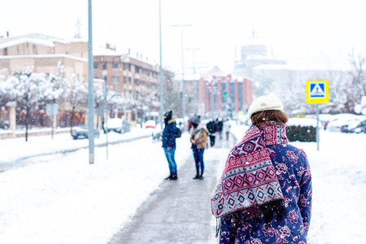 Rear view of people on street in winter