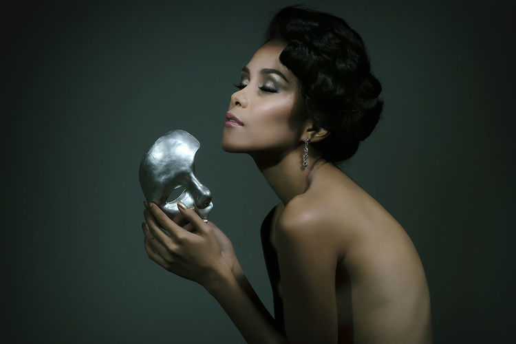 Side View Of Naked Fashion Model Holding Silver Mask Against Gray Background