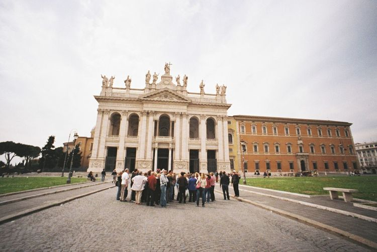 Group of tourists standing in front of classical building