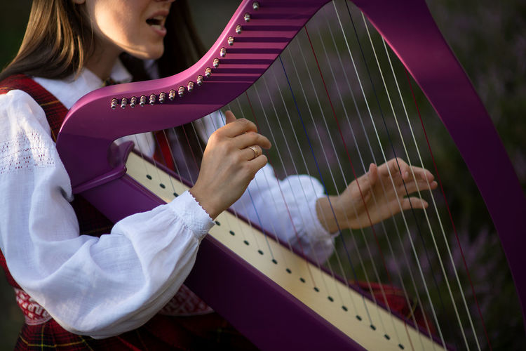 Midsection Of Musician Playing Celtic Harp