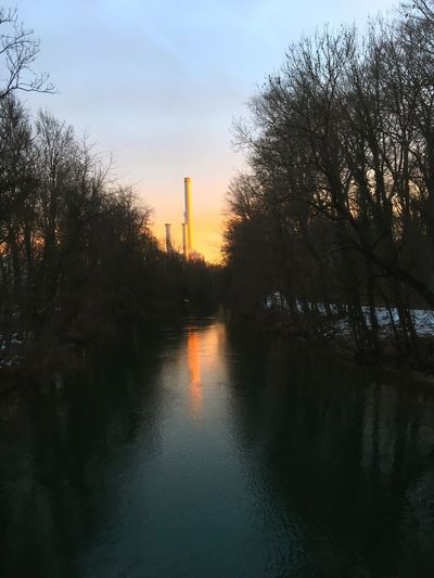 Isar Kanal mit Wasser, Bäumen, Himmel und Schornsteine von Heizkraftwerk in München. Tree Sky Water Plant Nature Reflection Architecture Building Exterior Built Structure Sunset Waterfront Beauty In Nature Outdoors Tranquility Factory Pollution No People