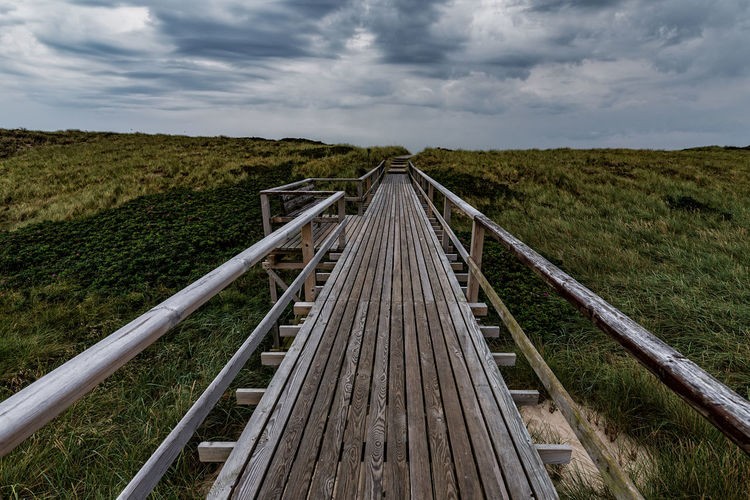 Boardwalk Amidst Landscape Against Sky