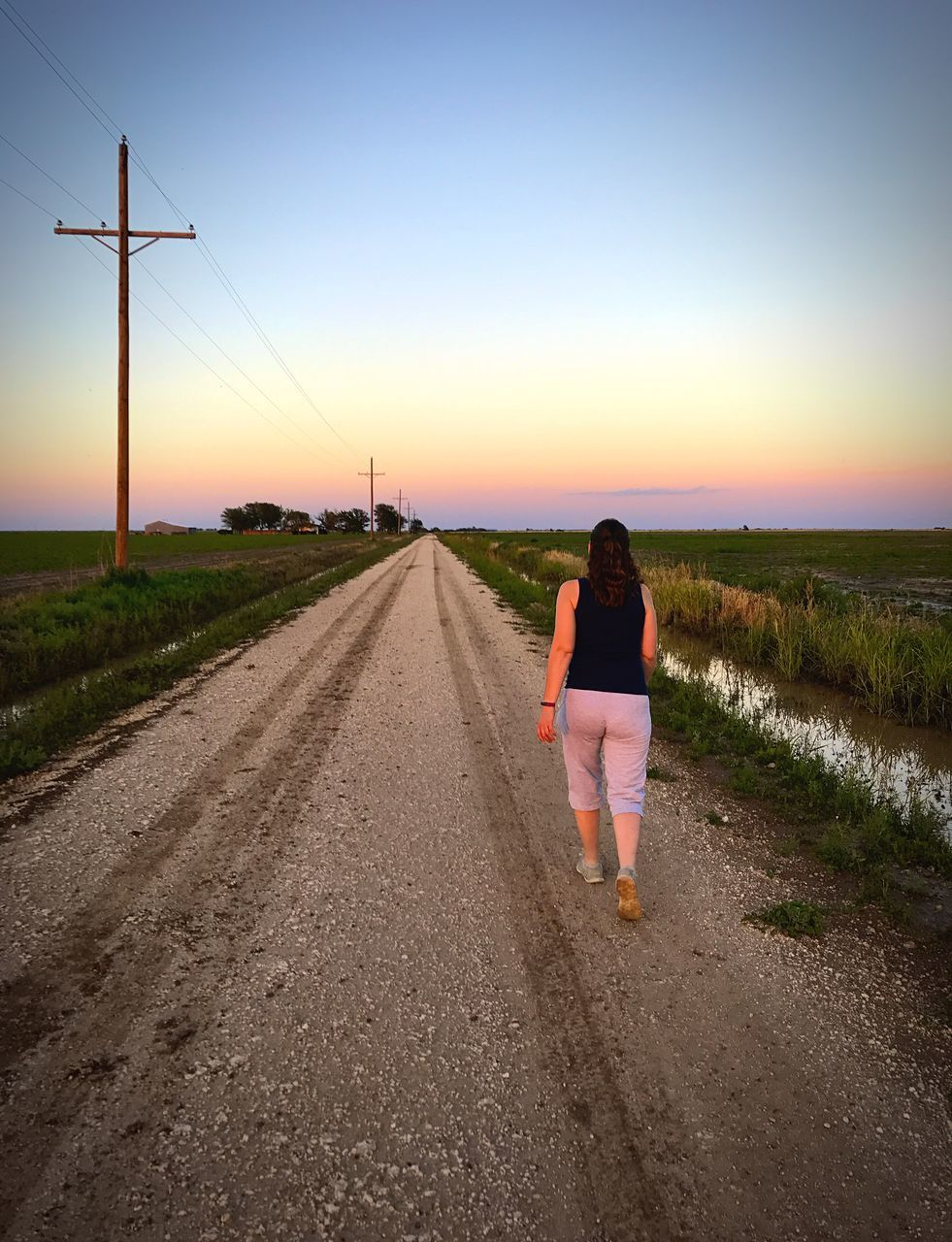 the way forward, rear view, full length, sunset, one person, real people, walking, lifestyles, sky, clear sky, transportation, nature, outdoors, leisure activity, road, scenics, grass, beauty in nature, day, young adult, people
