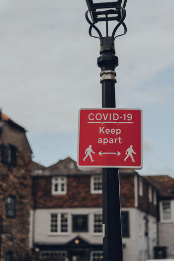 Red covid-19 keep apart sign on a sidewalk in rye, east sussex, uk, during covid 19 pandemic.