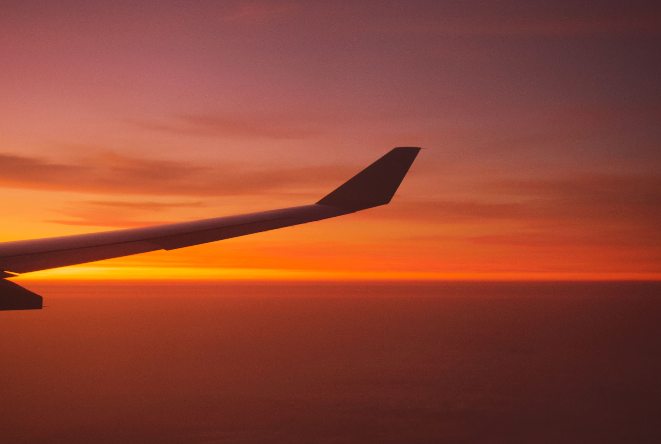 sunset, sky, airplane, orange color, air vehicle, cloud - sky, aircraft wing, beauty in nature, flying, scenics - nature, mode of transportation, no people, nature, mid-air, transportation, silhouette, outdoors, travel, tranquil scene, motion