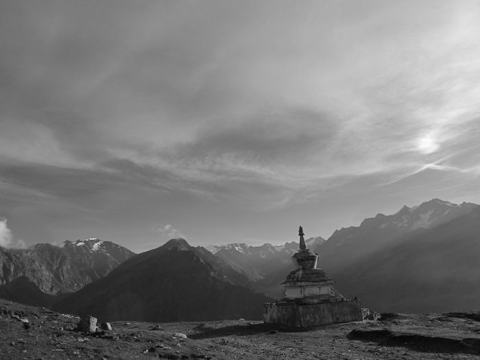 Stupa on mountain against cloudy sky during sunny day