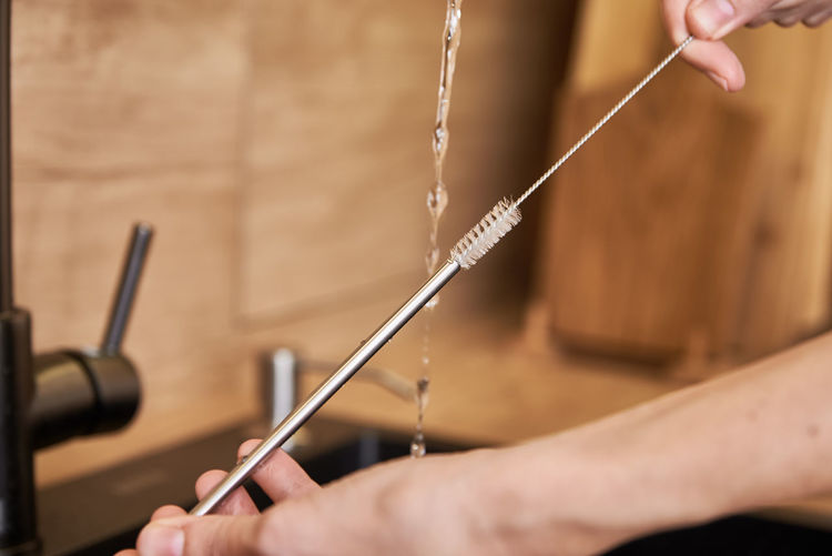Woman cleaning metal straw with organic brush. zero waste concept