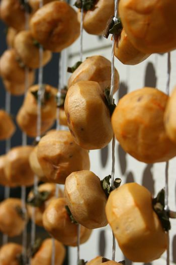 Close-up of persimmons hanging against wall