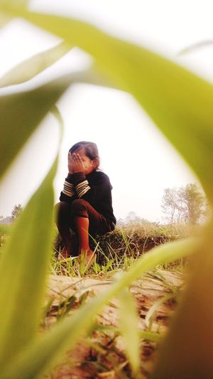 Girl with hands on face sitting over land