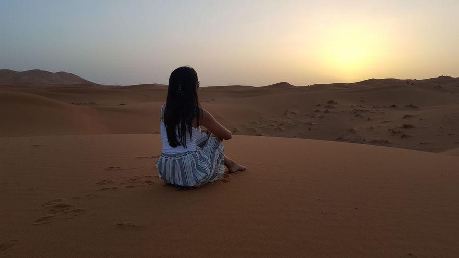 Woman sitting on sand dune at desert against sky