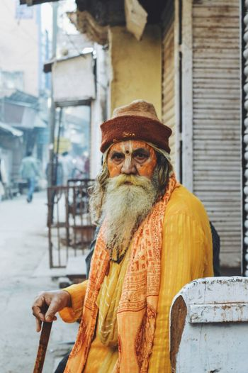 Close-up portrait of sadhu sitting against built structure in city
