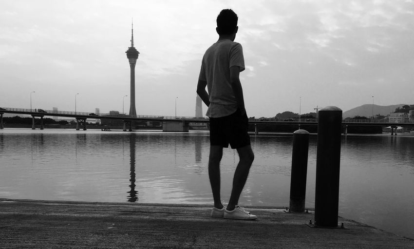 Rear view of man standing at pier over river against macao tower in city