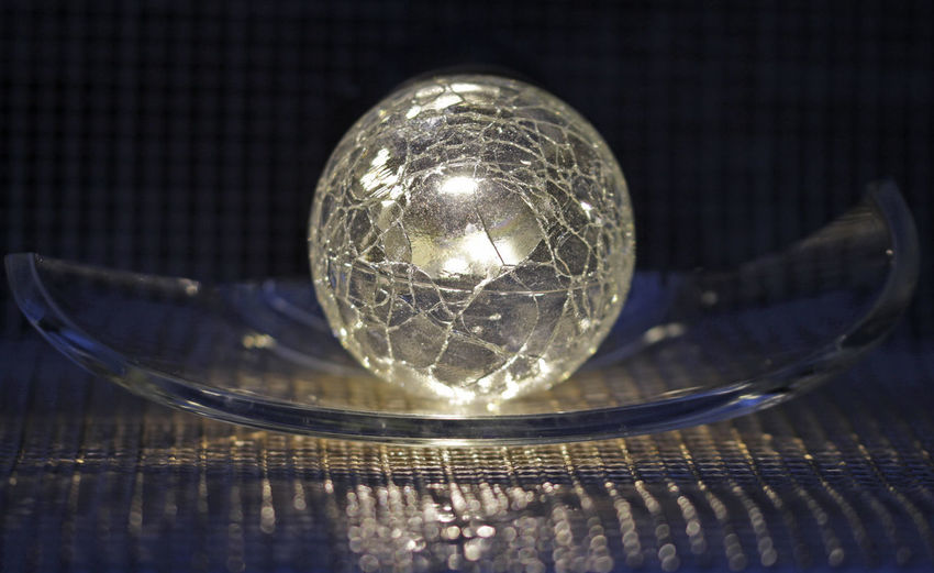 Close-up of crystal ball on glass table