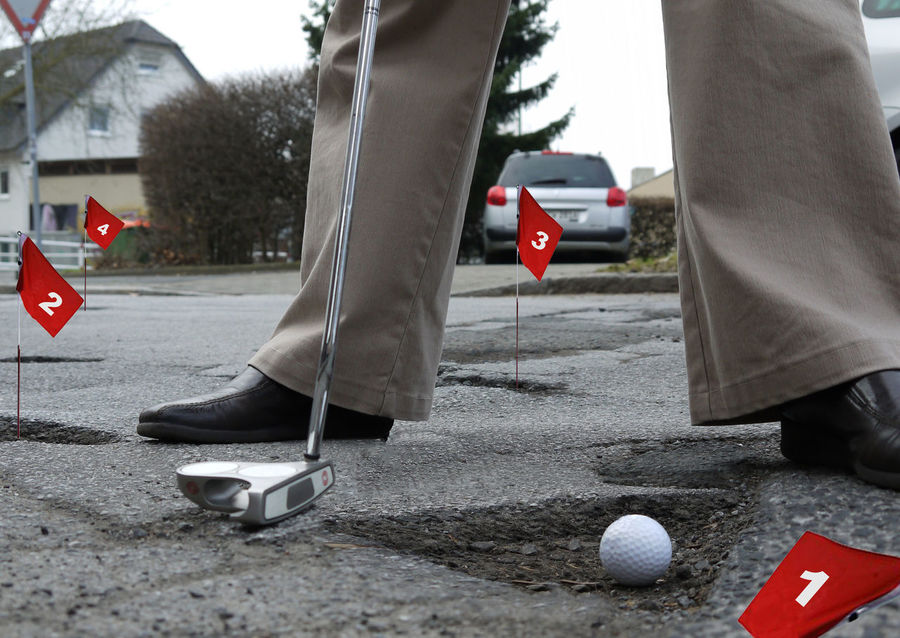 No money for road repairs, let's play golf Golf Golf Ball The Street Photographer - 2018 EyeEm Awards Ball Balloon Car City Damaged Damaged Surface Day Human Body Part Human Foot Human Leg Low Section One Person Outdoors Putting Putting In Work  Real People Red Road Shoe Street Surface Transportation