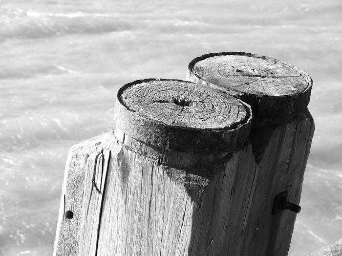 Close-up of old wooden post at beach against sky