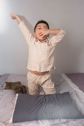Full length of a young man lying on bed