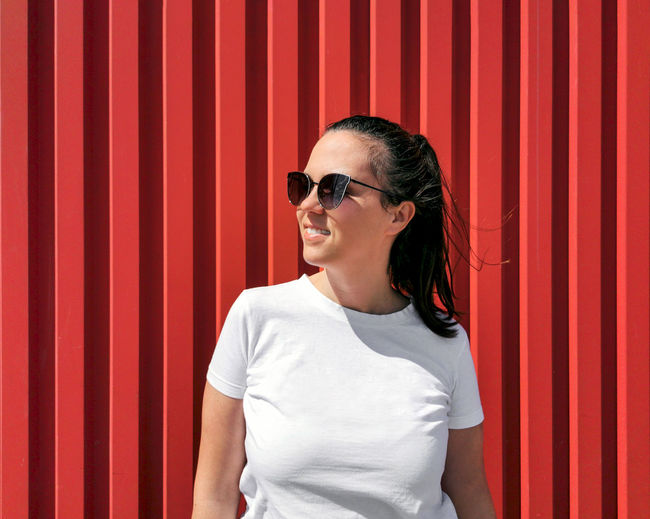 Portrait of a happy young woman in white t-shirt on red backgdrop.