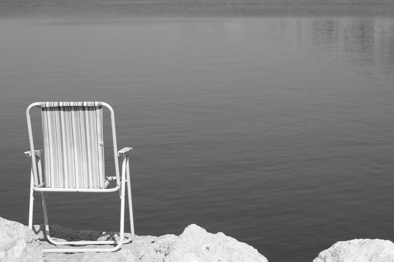 High angle view of empty chair by lake