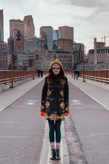 Portrait of smiling young woman standing on bridge in city