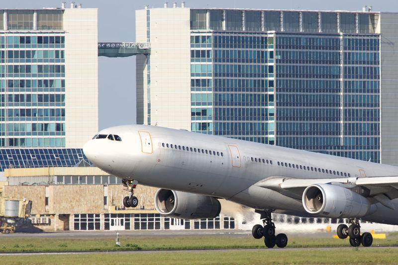 Airplane on airport runway against buildings in city