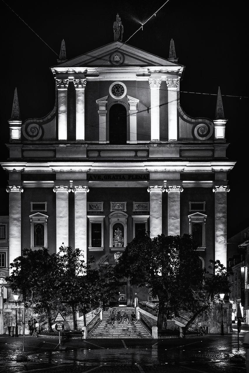 STATUE AGAINST ILLUMINATED BUILDINGS AT NIGHT