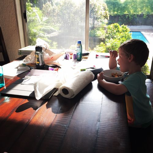 Side view of boy eating breakfast on table at home